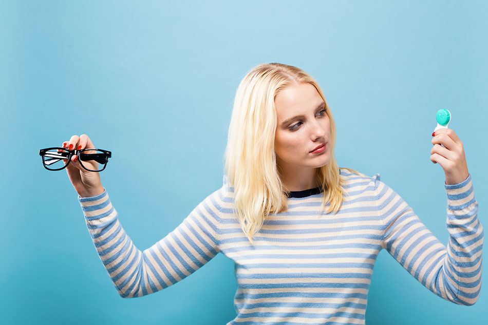 blonde woman deciding between contacts or glasses