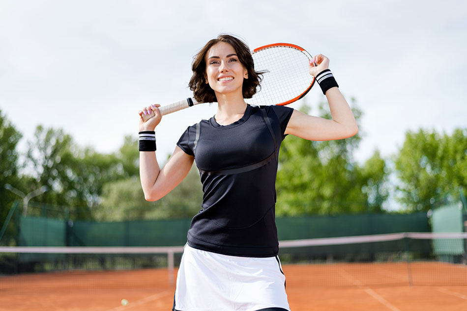 brunette woman with tennis racket on court