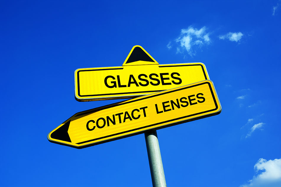 contact lenses vs glasses signpost on sky background