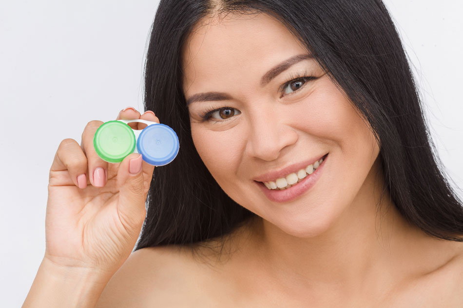 Happy woman holding contacts case