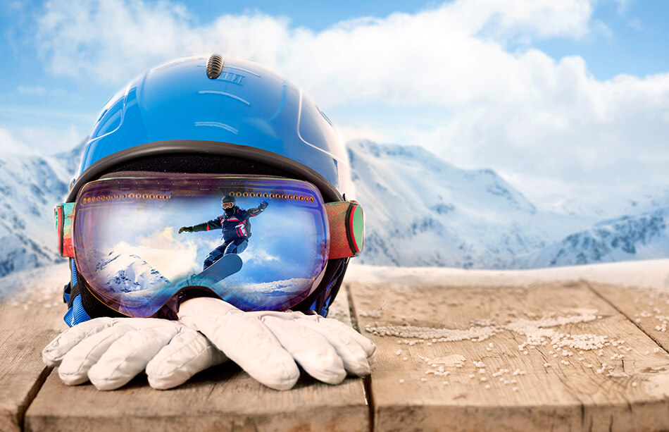 sports goggles, helmet and winter gloves with mountains in background