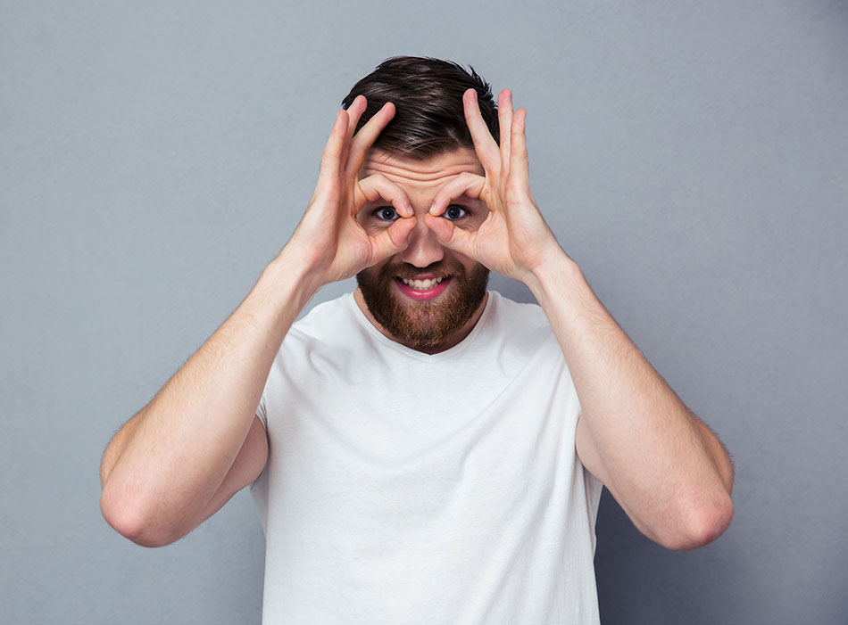 Man with hands as binoculars over eyes