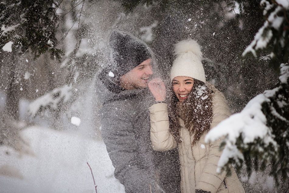 man and woman playing in snow