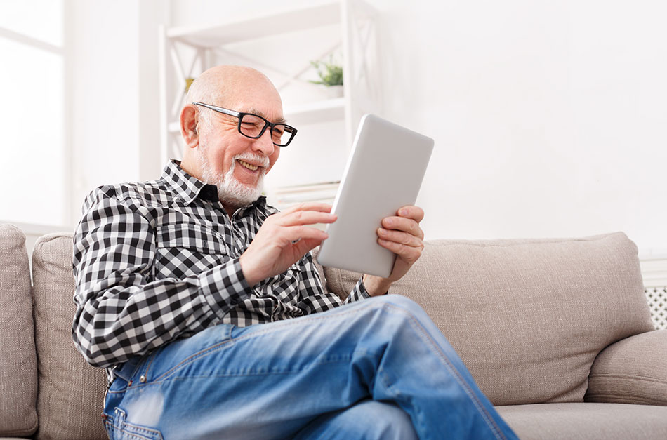 senior man wearing reading glasses holding tablet