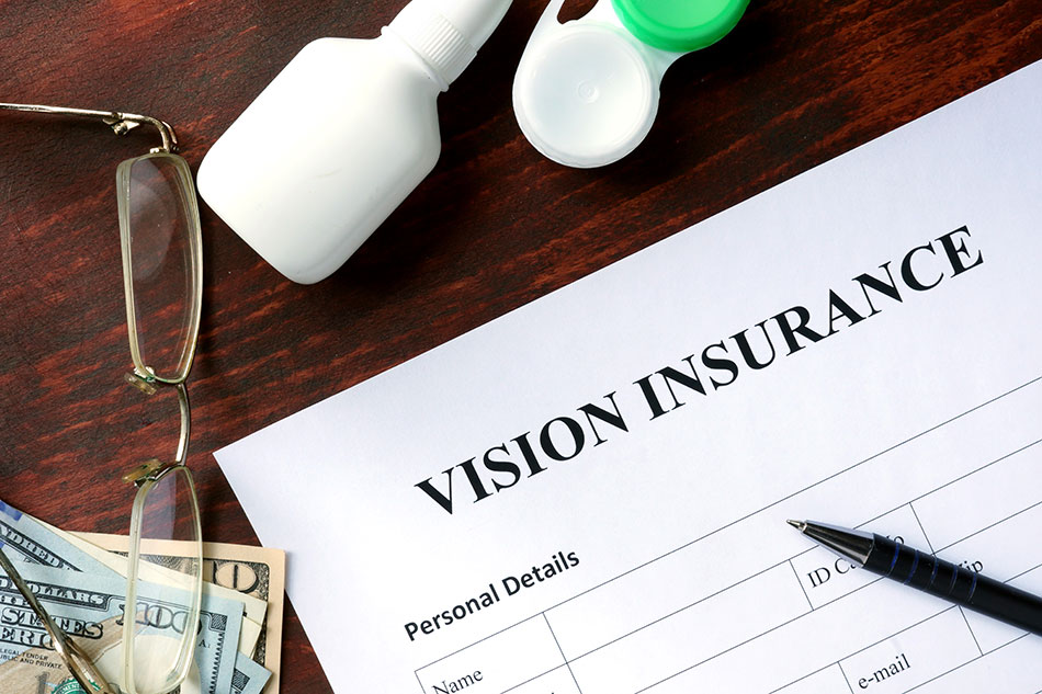 vision care insurance form on desk with pen, eyeglasses, money and contact lenses storage case.