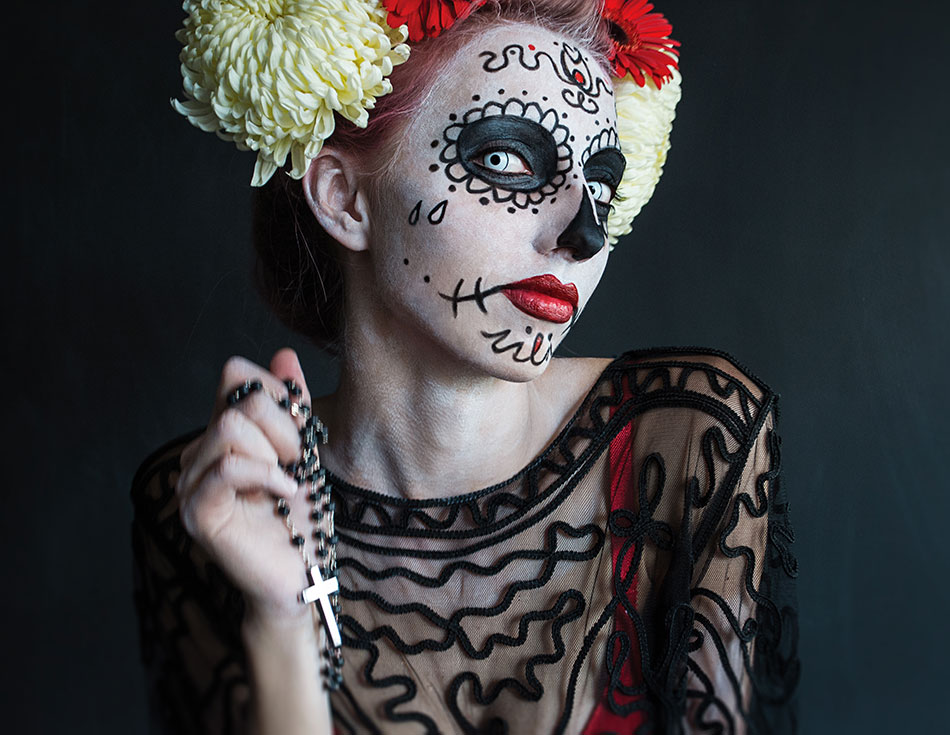 woman dressed in day of the dead costume with blue colored contact lenses