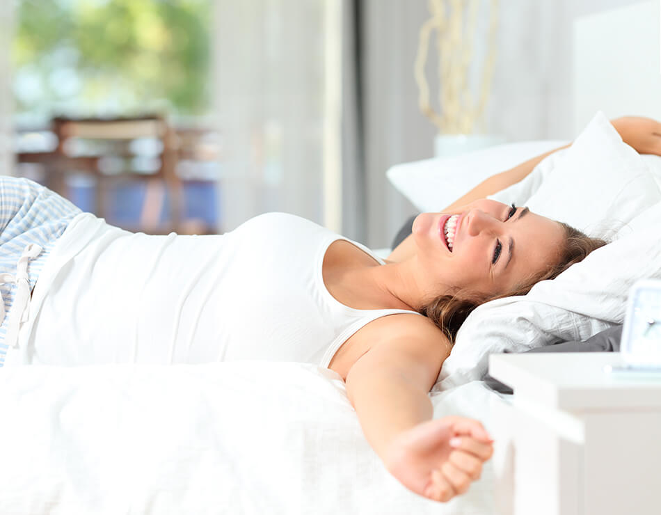 laughing woman waking up in bed