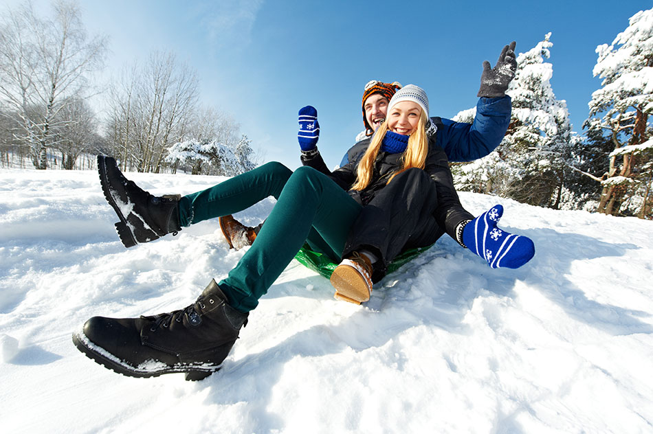 young couple sledding in snow