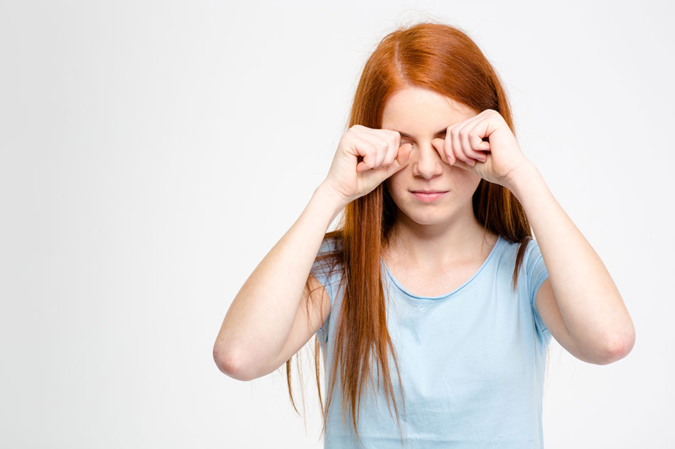 Young girl rubbing her eyes