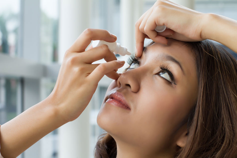 Young woman using eye drops